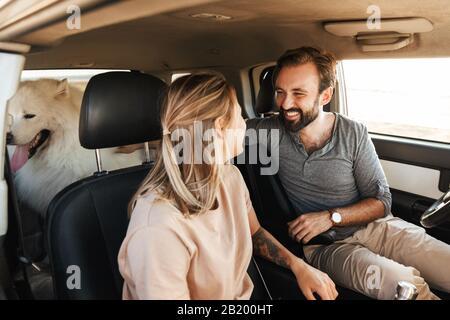 Image d'un jeune couple amoureux heureux avec chien samoyed plein air à la plage en voiture.