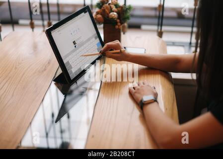 Gros plan sur les mains d'une jeune fille non reconnaissable qui écrit sur une tablette numérique.