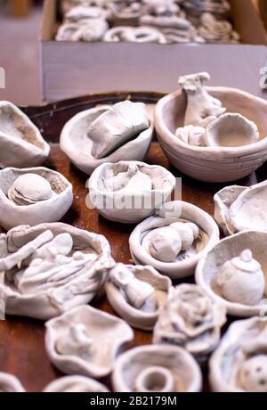 Les pots et bols crus sont séchage à l'air dans une salle de poterie, prêts à être glacés et tirés dans l'art décoratif Banque D'Images