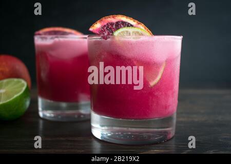 Margaritas d'orange du sang de coco : une paire de cocktails de tequila faits d'orange du sang, de chaux et de noix de coco
