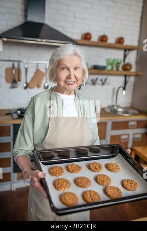 Femme âgée souriante ne tenant que des biscuits cuits au four