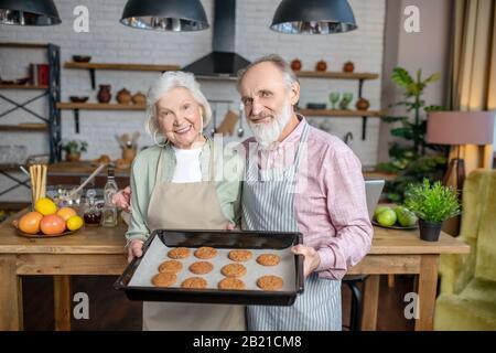 Heureux couple de personnes âgées cuisant des biscuits ensemble