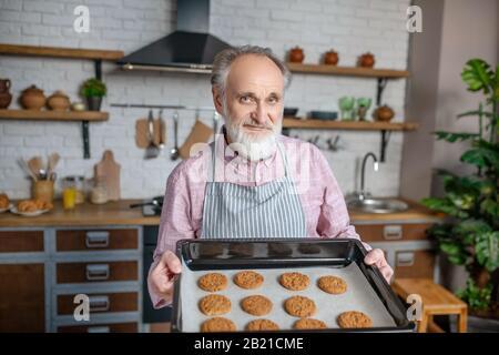 Un retraité souriant portant un tablier ne tenant que des biscuits cuits au four