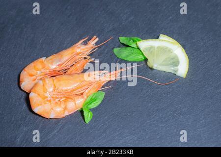 Deux crevettes rouges cuites au basilic vert et au citron sur fond noir Banque D'Images