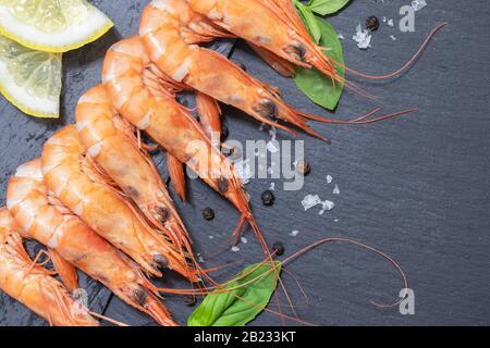 Crevettes rouges à l'arrière-plan noir avec citron et basilic Banque D'Images