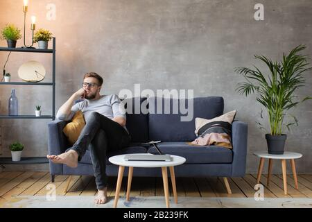 Homme inquiet assis sur le canapé à la maison. L'homme frustré et confus se sent mécontent, des problèmes dans la vie personnelle.