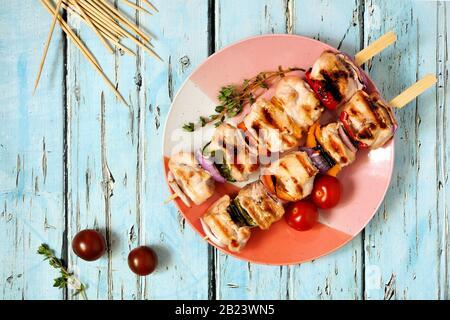 Brochettes de poulet et de légumes grillés sur plaque. Vue de dessus sur un fond en bois bleu. Concept de cuisine d'été.