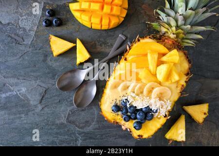 Bol à smoothie sain dans un ananas avec noix de coco, bananes, mangue et bleuets. Vue de dessus sur un fond en ardoise sombre. Espace de copie. Banque D'Images