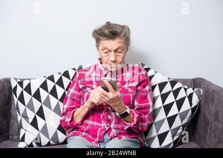 Vieux thème personne utilise la technologie. vieille femme aux cheveux gris et blancs avec les rides se trouve accueil dans la salle de séjour sur le canapé et utilise votre téléphone mobile en mains, l'air Banque D'Images
