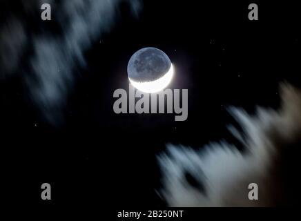 Une lune de croissant est encadrée par des nuages qui passent rapidement tandis que les étoiles brillent dans un ciel noir au-delà. Banque D'Images