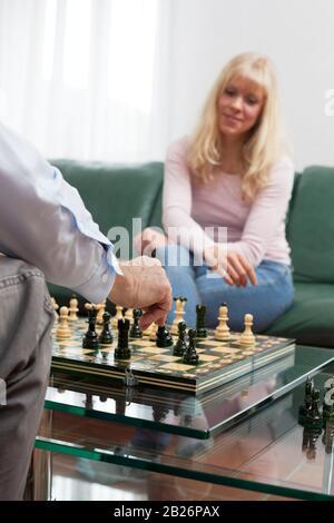 Jeune femme blonde souriante jouant aux échecs avec un homme dans un salon lumineux Banque D'Images