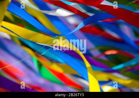 Beaucoup de rubans multicolores flutter dans le vent au soleil. Arrière-plan Banque D'Images