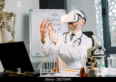 Médecin caucasien, scientifique, virologue, portant des lunettes de réalité virtuelle pour l'imagination, menant des recherches en laboratoire, tenant la fiole dedans Banque D'Images