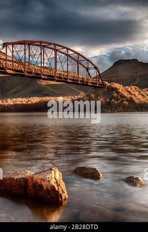 Long pont rouillé sous un ciel nuageux dans une scène de désert élevé regardant vers le haut du bord de l'eau