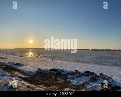 Coucher de soleil sur les rives de la Volga gelée. Les rayons du soleil se reflètent sur la glace. Dans la distance vous pouvez voir la silhouette d'un homme. Copier Banque D'Images