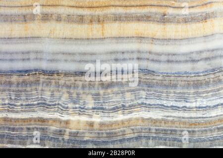 La texture du marbre beige avec des rayures horizontales grises, brunes et beiges ondulées. Surface polie. Banque D'Images