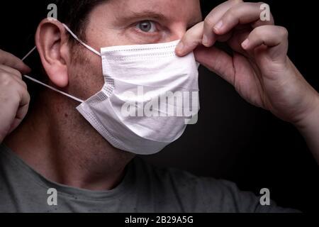 Homme caucasien mettant sur un masque de visage avec une main mettant la bande élastique sur une oreille et avec l'autre serrer la pièce en métal autour du nez