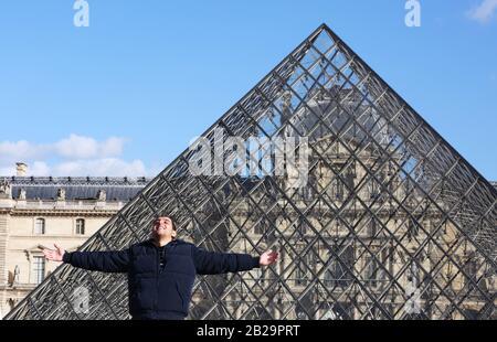 Paris. 11 mars 2019. Photo de dossier prise le 11 mars 2019 montre un touriste posant pour une photo devant le Musée du Louvre à Paris, France. Le musée du Louvre a été fermé le 1er mars en raison de l'épidémie de coronavirus qui s'étend. Crédit: Gao Jing/Xinhua/Alay Live News Banque D'Images
