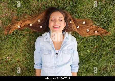 Jolie fille rêvant de se coucher sur l'herbe avec des fleurs de daisies dans ses cheveux Banque D'Images
