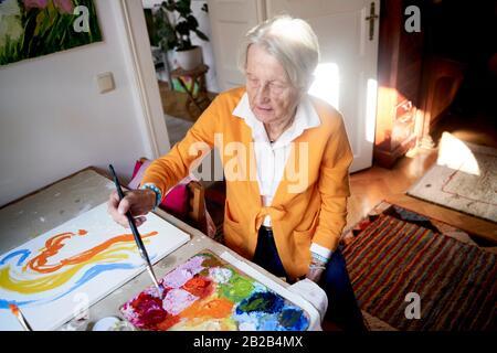 Femme senior peinture à la maison Banque D'Images
