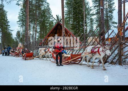 Rovaniemi, Finlande, Touristes sur les traîneaux à rennes dans le village et le parc du Père Noël