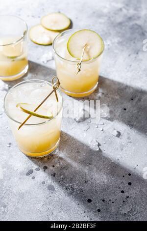 Cocktail de poire froide ou queue de bœuf avec purée de soda et de poire et tranches de fruits en verre court sur fond gris avec ombre. Boisson rafraîchissante en été