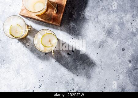 Cocktail de poires froides avec purée de soda et de poire et tranches de fruits en verre court sur fond gris avec ombre.boisson rafraîchissante d'été avec glace