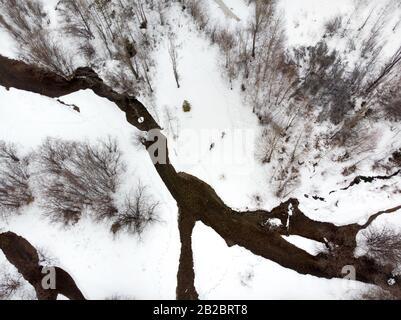 Deux touristes sont en randonnée dans la vallée de montagne avec rivière et neige à l'hiver à Almaty, au Kazakhstan. Vue de dessus aérienne, tir drone. Banque D'Images
