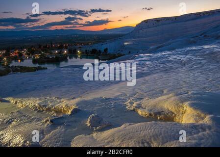 Travertines blanches illuminées de Pamukkale en premier plan (Turquie). Coucher de soleil sur les montagnes en arrière-plan. Banque D'Images