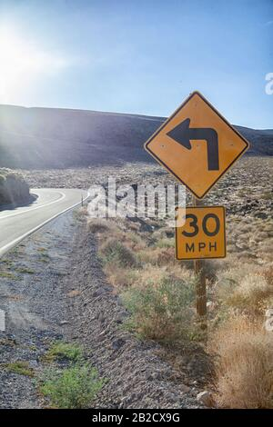 Le panneau jaune indique un virage à gauche et indique une limite de vitesse de trente miles par heure sur une route sinueuse traversant le parc national de la Vallée de la mort Banque D'Images