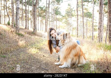 jeune femme belle avec de longs cheveux marchant avec le chien de collie. Plein air dans le parc. Près de la mer, la plage d'été