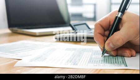 Gros plan du formulaire d'impôt américain 1040 et calcul et remplissage manuel du papier de rapport avec un ordinateur portable au bureau.