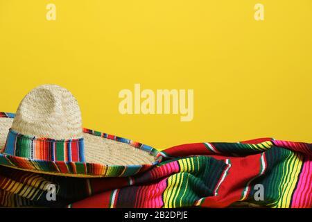 Sombrero mexicain sur une couverture en serape colorée sur un fond jaune. Thème Cinco de Mayo