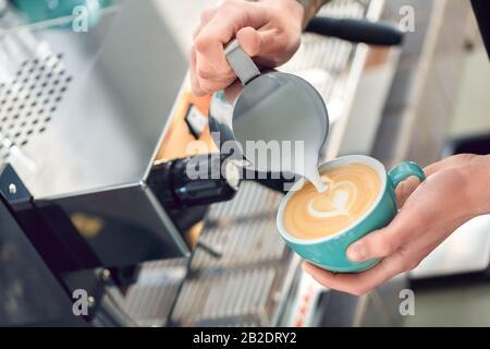 Café Passion. Jeune barista du café qui verse du lait cuit à la vapeur dans une tasse pour faire du latte art cœur gros plan Banque D'Images