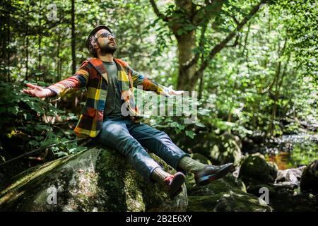 Un jeune homme barbu est assis sur la pierre dans la forêt et profitant de la nature. Un homme qui cherche avec des bras ouverts et rêvant Banque D'Images