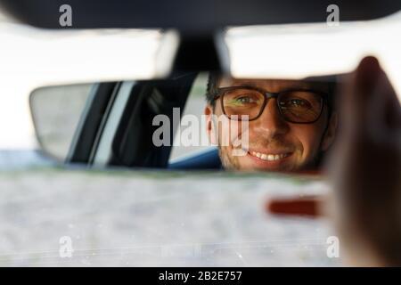 Homme joyeux et joyeux portant des lunettes et un miroir de réglage tout en étant assis dans sa voiture, regardant en réflexion. Mise au point douce. Émotions de conduire une nouvelle voiture