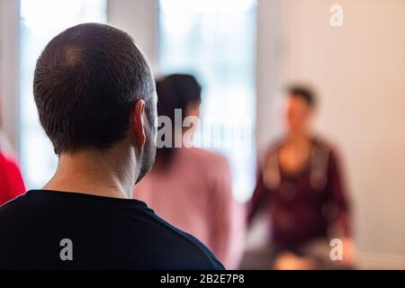 L'homme s'engageant dans le yoga. Vue arrière d'un homme qui pratique le yoga en classe spéciale. Le gars qui apprend le yoga dans un centre spécial Banque D'Images