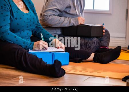 Le couple marié prend des notes pendant le cours de yoga. L'étude des gens de yoga en prenant des notes sur un bloc-notes. Un homme d'écriture et une femme Banque D'Images