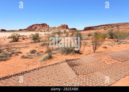 Sentier de randonnée devant le escarpement en grès de la vallée de l'Arc-en-ciel et son claypan, au sud d'Alice Springs, territoire du Nord, territoire du Nord, Australie