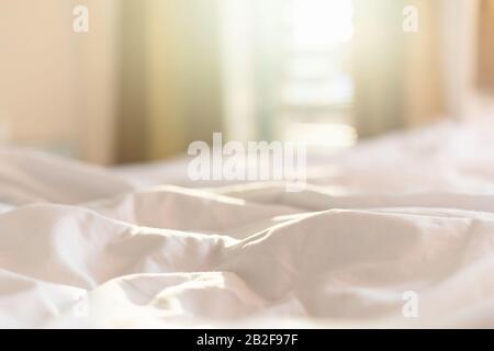 Gros draps blancs et oreiller dans la chambre de l'hôtel le matin avec lumière du soleil depuis les fenêtres Banque D'Images