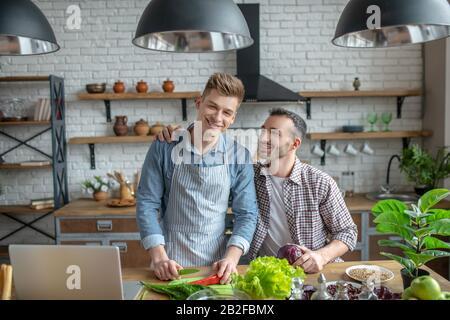 Jeune couple gay qui fait le petit déjeuner ensemble et souriant