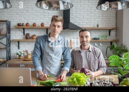 Un jeune couple gay passe du temps à la maison pour cuisiner le petit déjeuner