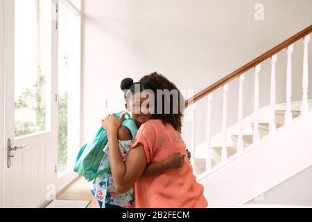 Vue latérale d'une femme afro-américaine et de sa fille à la maison embrassant dans le couloir avant de partir pour l'école. Famille profitant du temps à la maison, la vie Banque D'Images