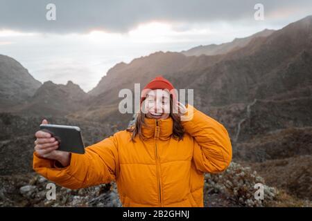 Portrait d'un jeune voyageur vêtu d'une veste et d'un chapeau lumineux pour un voyage en montagne, voyageant sur l'île de Tenerife, Espagne