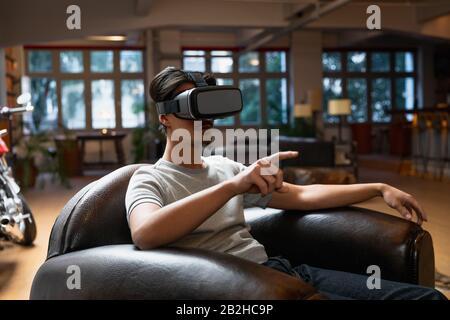 Jeune homme utilisant un casque VR Banque D'Images
