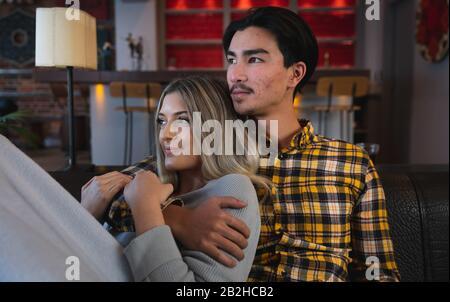 Jeune couple embrassant et regardant loin