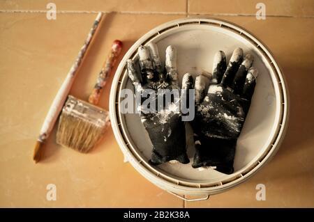 Peinture sur le sol après utilisation. Peindre des gants, une casserole et des brosses avec de la peinture blanche au milieu d'une maison en construction. Banque D'Images