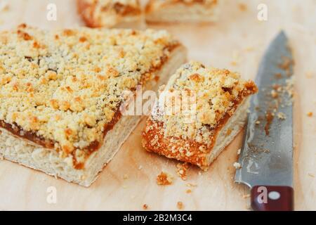 Tarte au sable doux avec confiture d'abricot. Couper en morceaux, allongé sur un panneau avec une bouilloire en arrière-plan. Théière avec tasses de thé et gâteau sucré