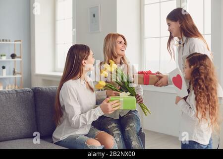 Bonne Fête Des Mères. Enfants filles donner à maman un bouquet de fleurs à la maison.