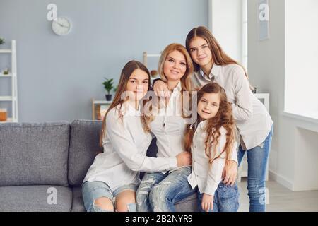 Bonne fête des mères. Une mère et trois filles sur le canapé dans la chambre.